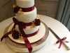 Winter themed wedding cake with deep red Sugar Roses, gold foliage & Monogram